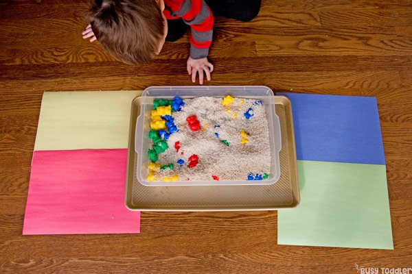 A toddler playing with a sorting and sensory activity from Busy Toddler