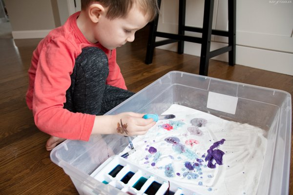Preschooler playing a science activity with baking soda and vinegar in a storage bin