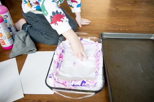 A child playing with a marbled art shaving cream activity