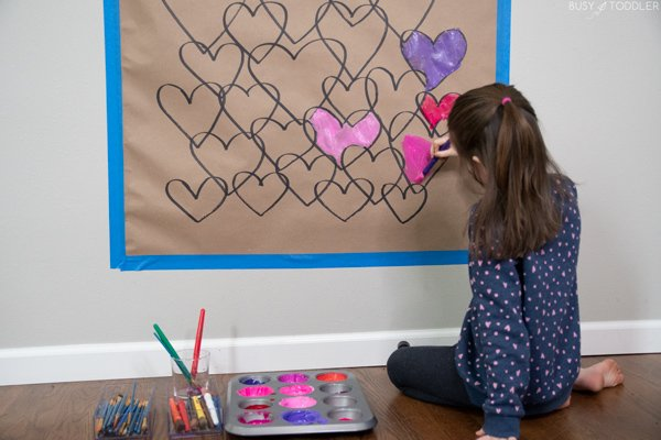 A kindergartener painting overlapping hearts in a Valentine's Day activity