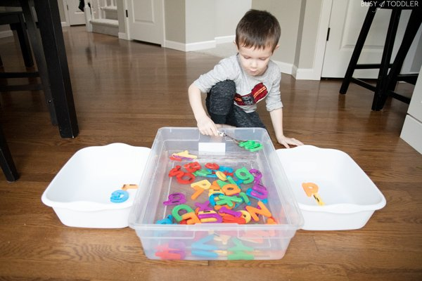 Kids playing a scooping activity from Busy Toddler