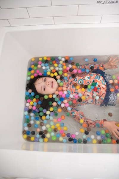 A child plays in a bath filled with pom pom balls