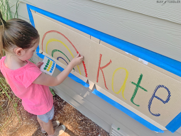 A child playing with dot stickers in a fine motor activity line up