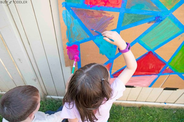 Kids doing an awesome tape resist art activity for kids this summer