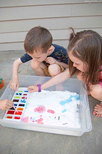 Kids playing with an outdoor science activity experimenting with baking soda and vinegar