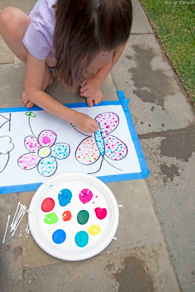 A child paints a butterfly using pointillism