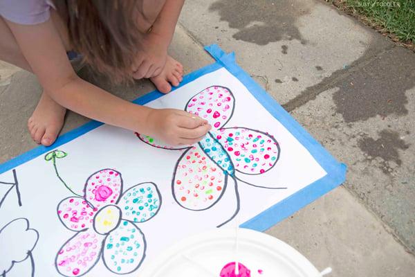 A child explores pointillism in a kids activity