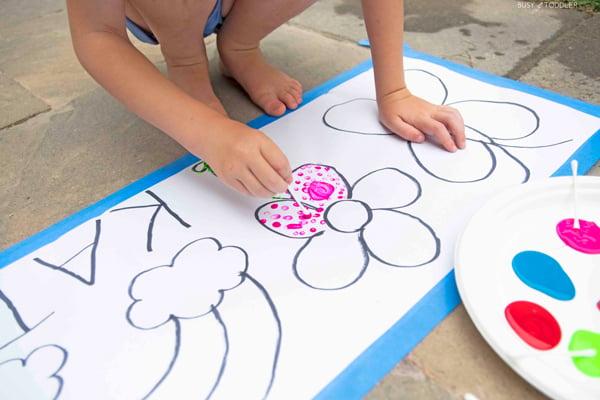 A child paints a flower pink using pointillism