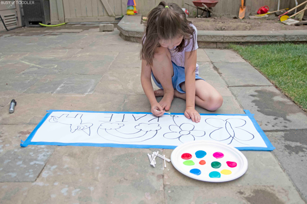 A child sits ready to use a q-tip in a pointillism activity