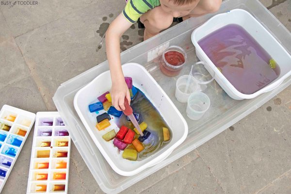 A child experimenting with colored ice and warm water