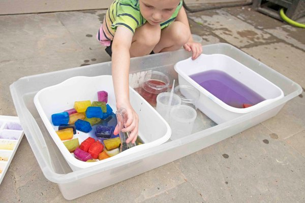 A child playing at an outdoor colored ice bin