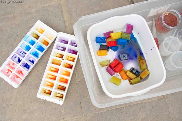 A child playing with colored ice cubes