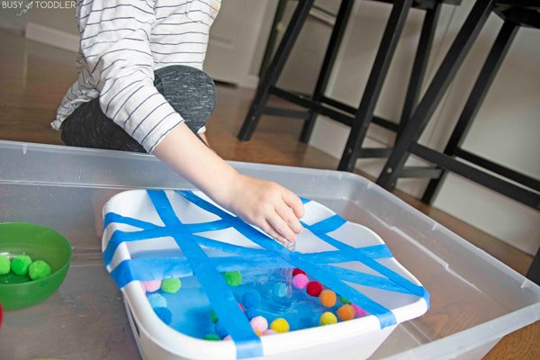 A child sorting pom pom balls in a kids activity