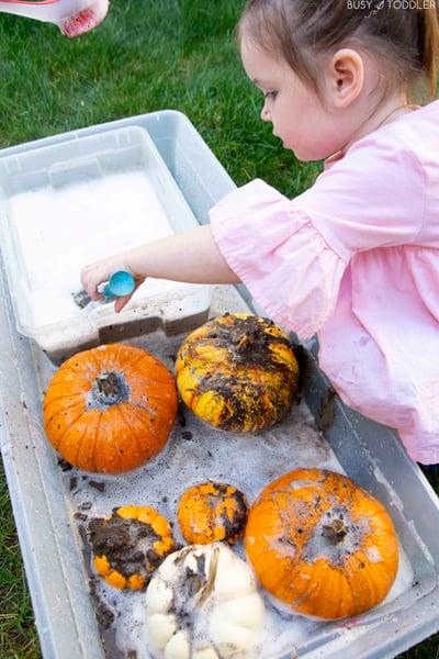 A preschooler doing a pumpkin washing activity