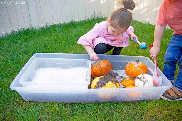 A toddler and a preschooler doing a pumpkin washing activity