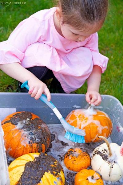 A preschooler and a toddler doing a pumpkin washing activity